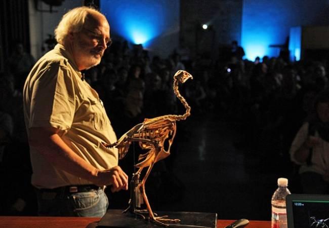 Профессор Джек Хорнер на лекции демонстрирует подобие скелетов птицы и динозавра.